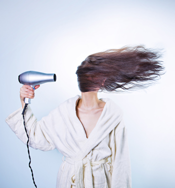 Woman with overpowered hairdryer